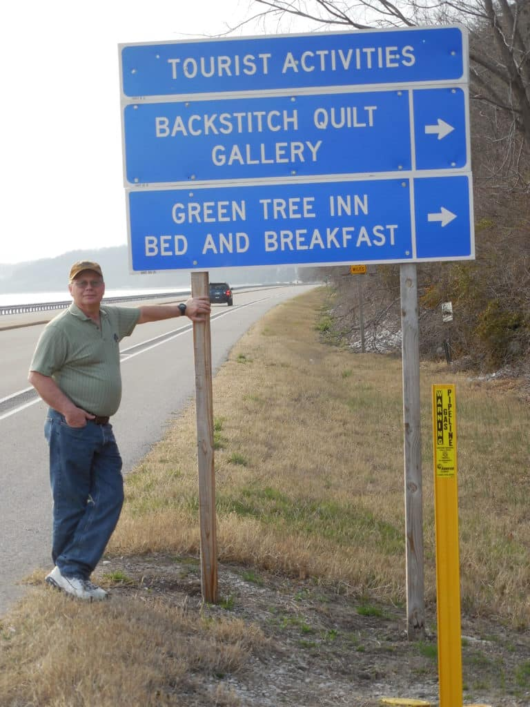 Gary standing beside IDOT transportation sign along the Great River Road