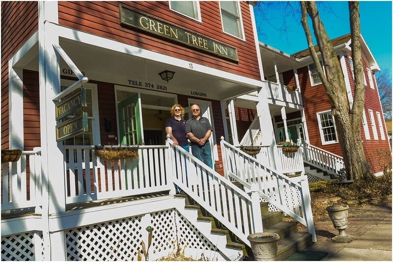 Gary and Connie on stairs with white railing leading up to red building with Green Tree Inn sign.