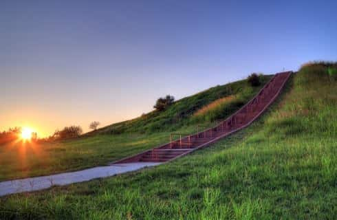 Small hill with rolling grass and stairwell to the top of the hill at sunset
