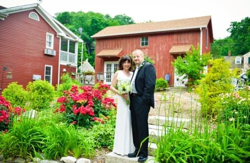 Bride and groom standing in backyard garden with green and red shrubs