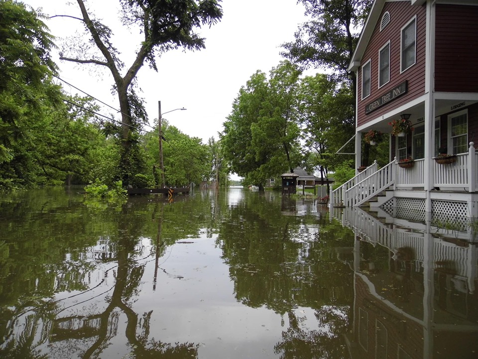 Red Building with sign Green Tree Inn on side, white stairs covered with water, Trees surrounding flooded street.