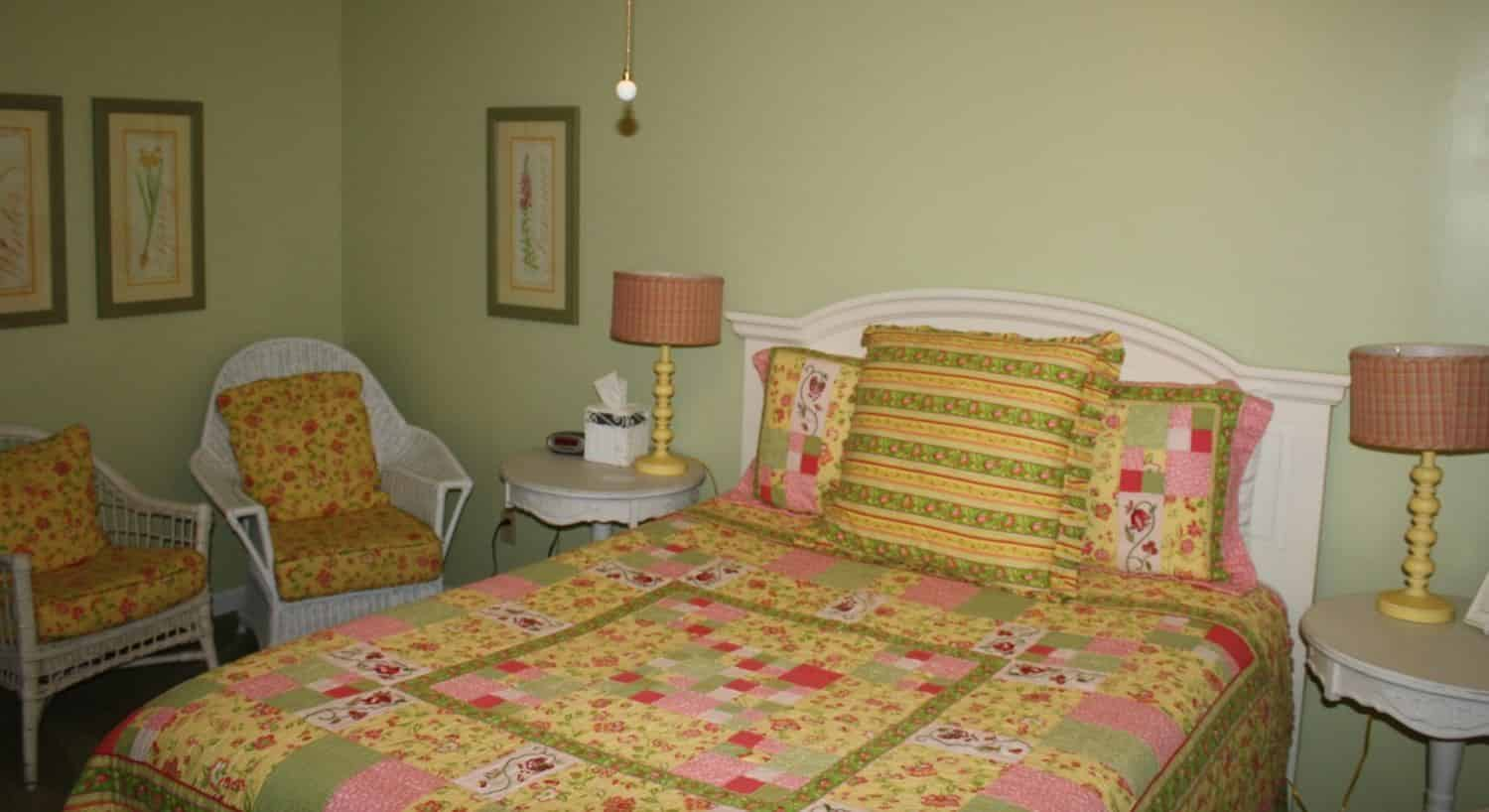 Bedroom painted light green with white headboard and green, yellow, and pink bedding and white wicker chairs