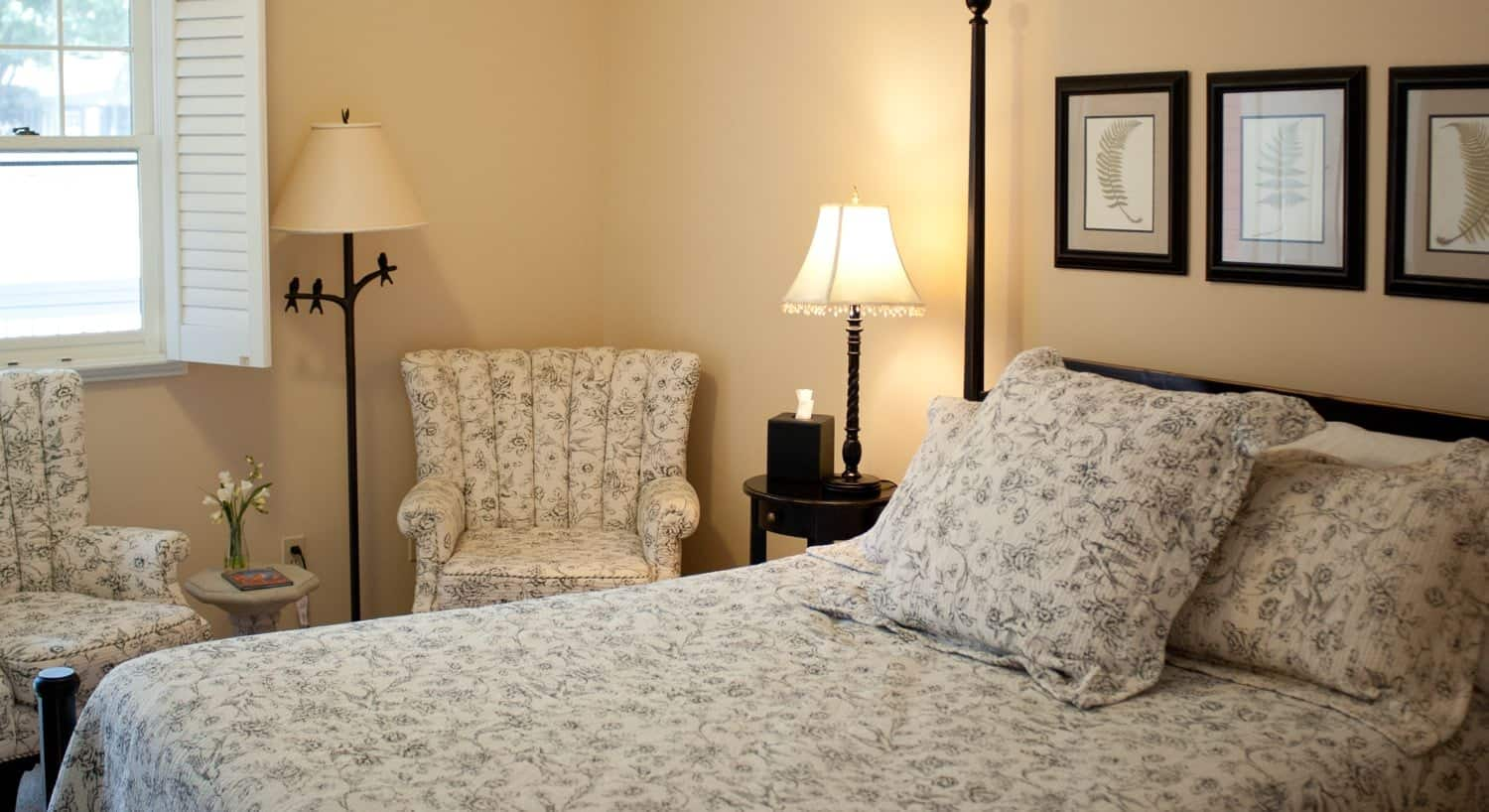 Dark wood four-post bed with floral bedding and chairs to match