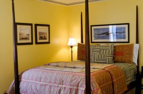 Bedroom painted yellow with dark wooden four-post bed with multicolored bedding