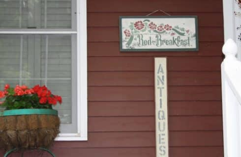 Front of house painted dark red and white with large potted flowers near window and Bed and Breakfast sign