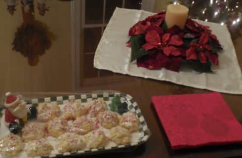 Christmas cookies on a green and white tray next to red napkins and poinsettia candle ring