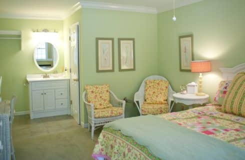 Bedroom painted light green with bed, two chairs, and two dressers