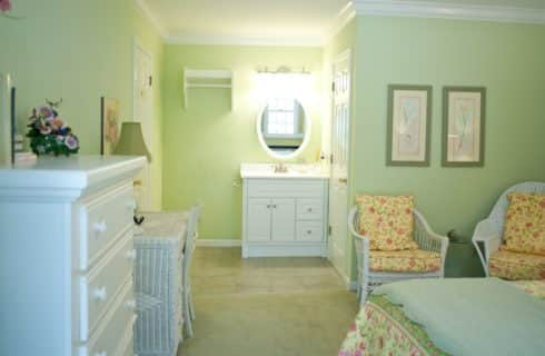 Bedroom painted light green with white furniture and yellow, pink, and green upholstered chairs and bedding