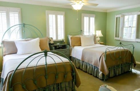 Two full size beds with neutral colored bedding in light green room