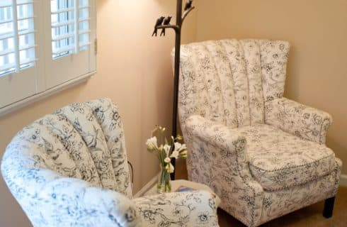 Floral upholstered chairs next to rod-iron floor lamp