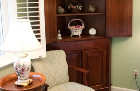 Dark wooden cabinet next to sage upholstered chair