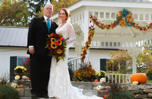 bride holding bouquet with fall flowers and groom standing by white gazebo with draping fall flowers house with green shutters in distance