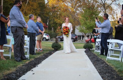 bride walking down aisle with guests standing by white chairs on both sides taking pictures with cell phones