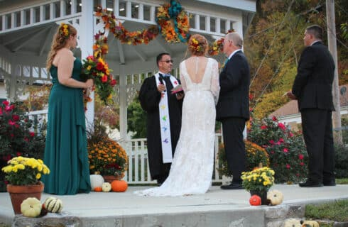 bride and groom standing in front of minister by white gazebo, best man and maid of honor standing next to couple