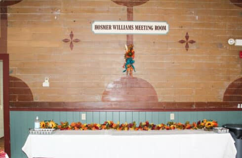 hosmer williams meeting room on brown wood with buffet table with white table close decorated with fall flowers and flower arrangement hanging on wall