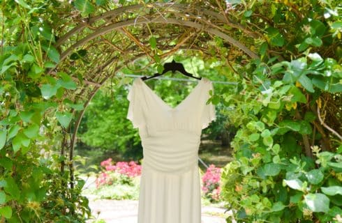 White wedding dress hanging from arched arbor in garden