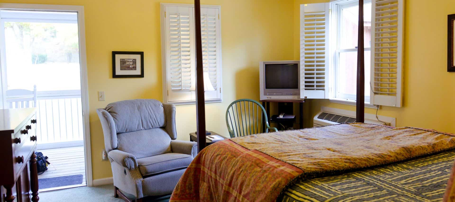 Bedroom painted yellow with dark wooden four-post bed