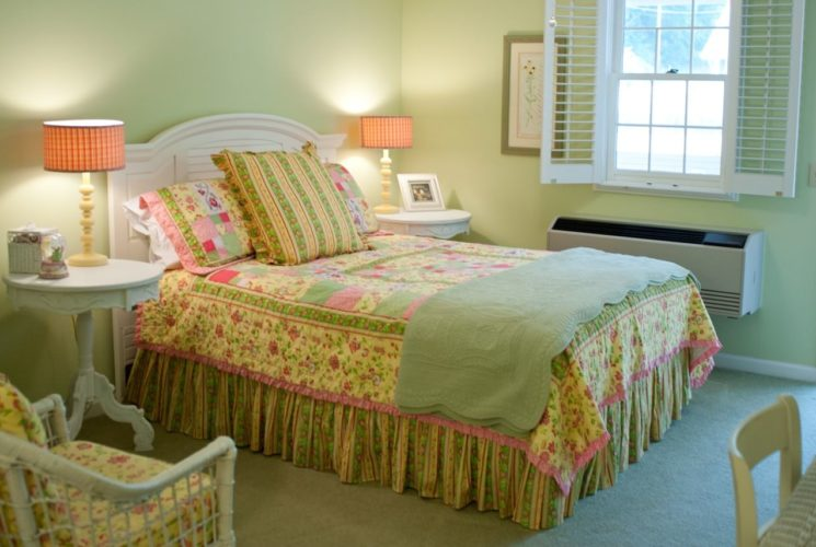 White headboard with sage blanket and green, yellow, and pink comforter next to white side tables