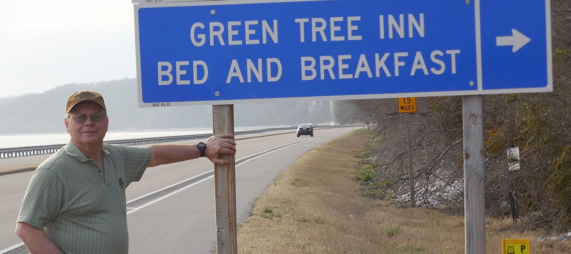Person standing next to blue highway sign with Green Tree Inn Bed and Breakfast written on it