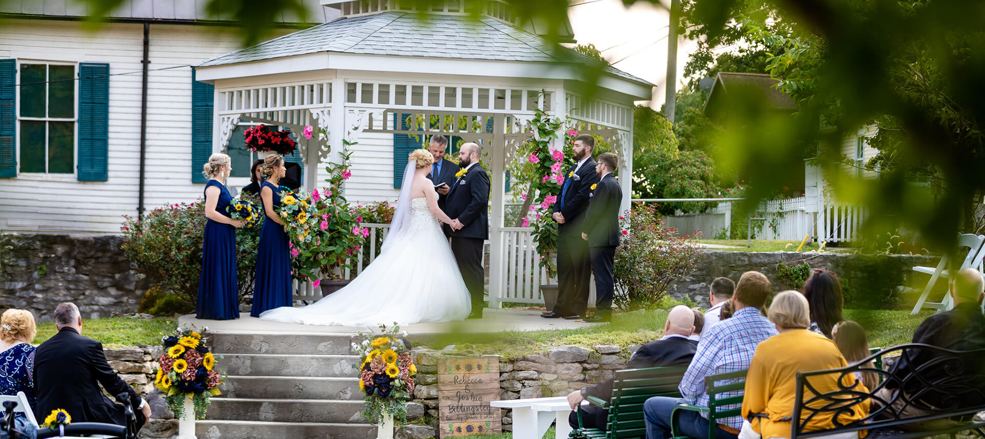 Bride in front of old church painted white with dark shutters