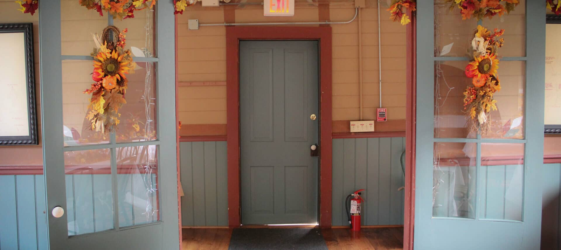 gray double glass paned doors with fall flowers arrangements facing hallway with black carpet runner, fire extinguisher, exit sign and fire alarm