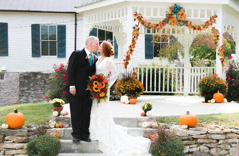 bride holding fall flower bouquet and groom standing on stairs kissing white gazebo in background with fall flowers hanging