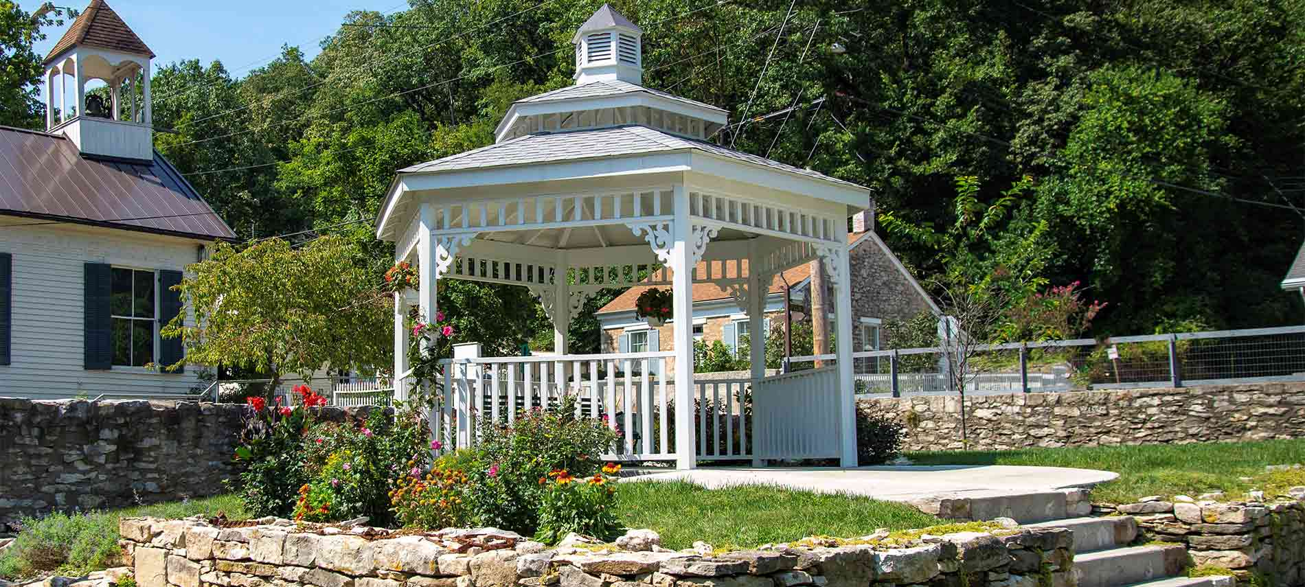 A stone lined raised gazebo with turret top and decorative sides outside the inn.