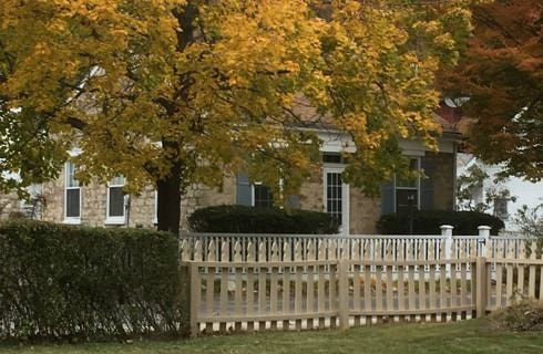 Stone bricked house with white picket fence and tree with yellow and green leaves